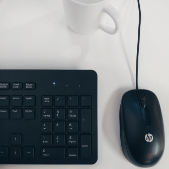 Keyboard, mouse, and white cup