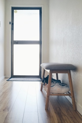 Hallway with a door, floor mat, and a bench with some shoes