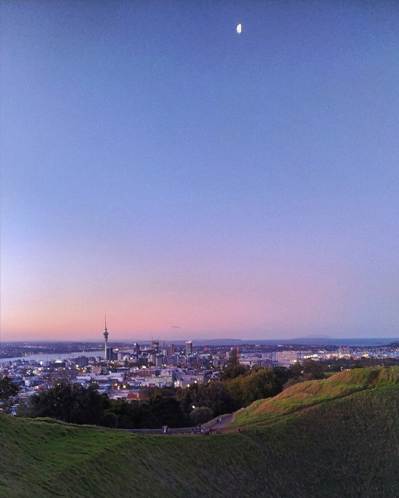 Overlooking Auckland from Mt. Eden, with pastel skies and a half moon