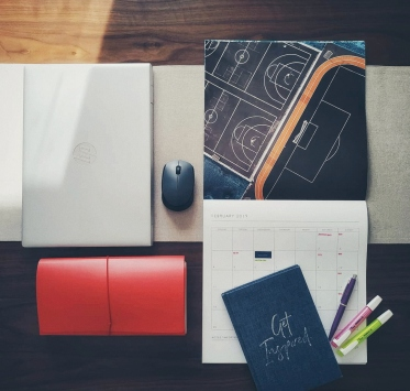 Laptop, calendar, journal, and pens
