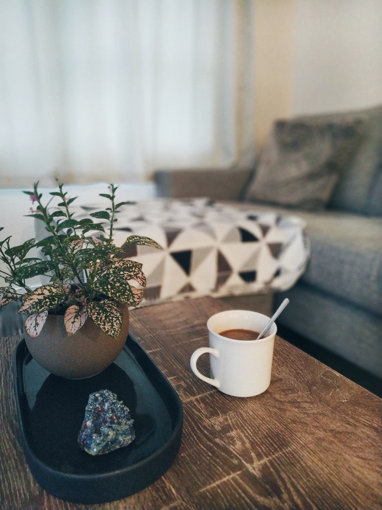 Coffee and plant in a table, with a couch at the back