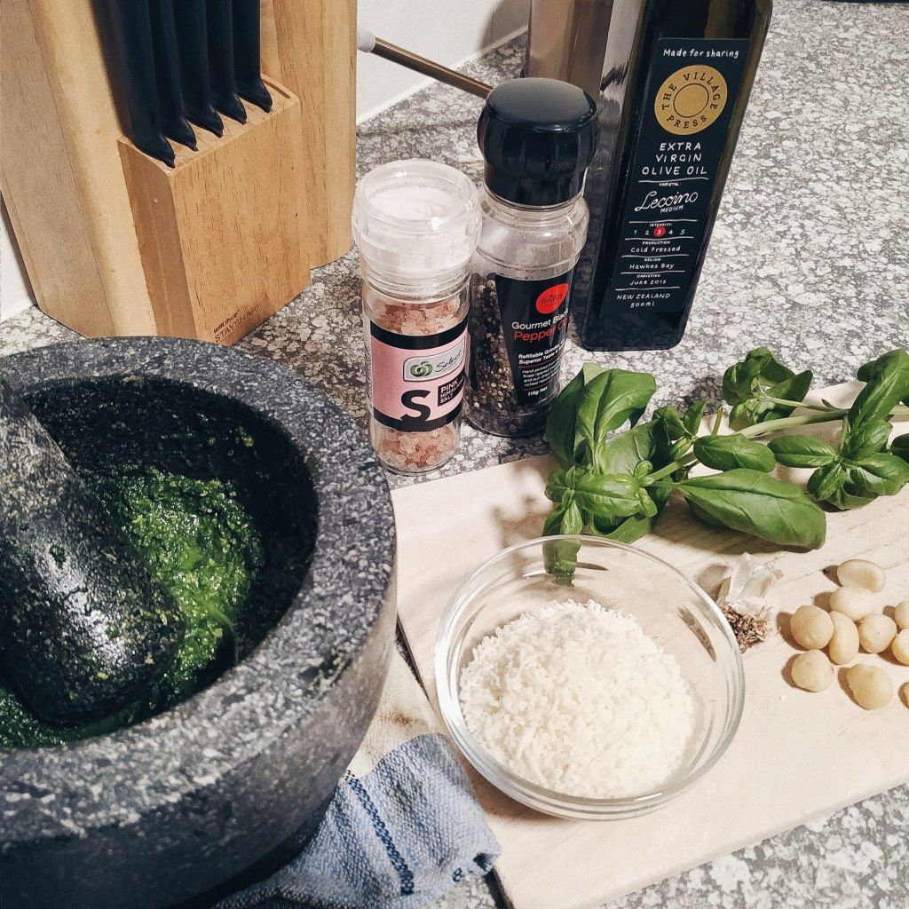 Mortar and pestle, salt and pepper, olive oil, basil leaves, cheese, garlic and nuts
