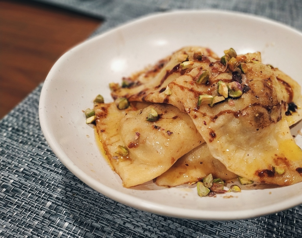 Ravioli with balsamic brown butter sauce topped with chopped pistachios