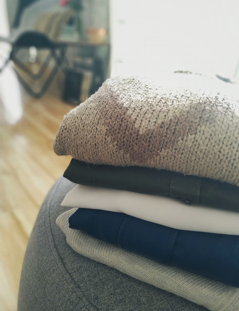 A stack of folded, thrifted clothes