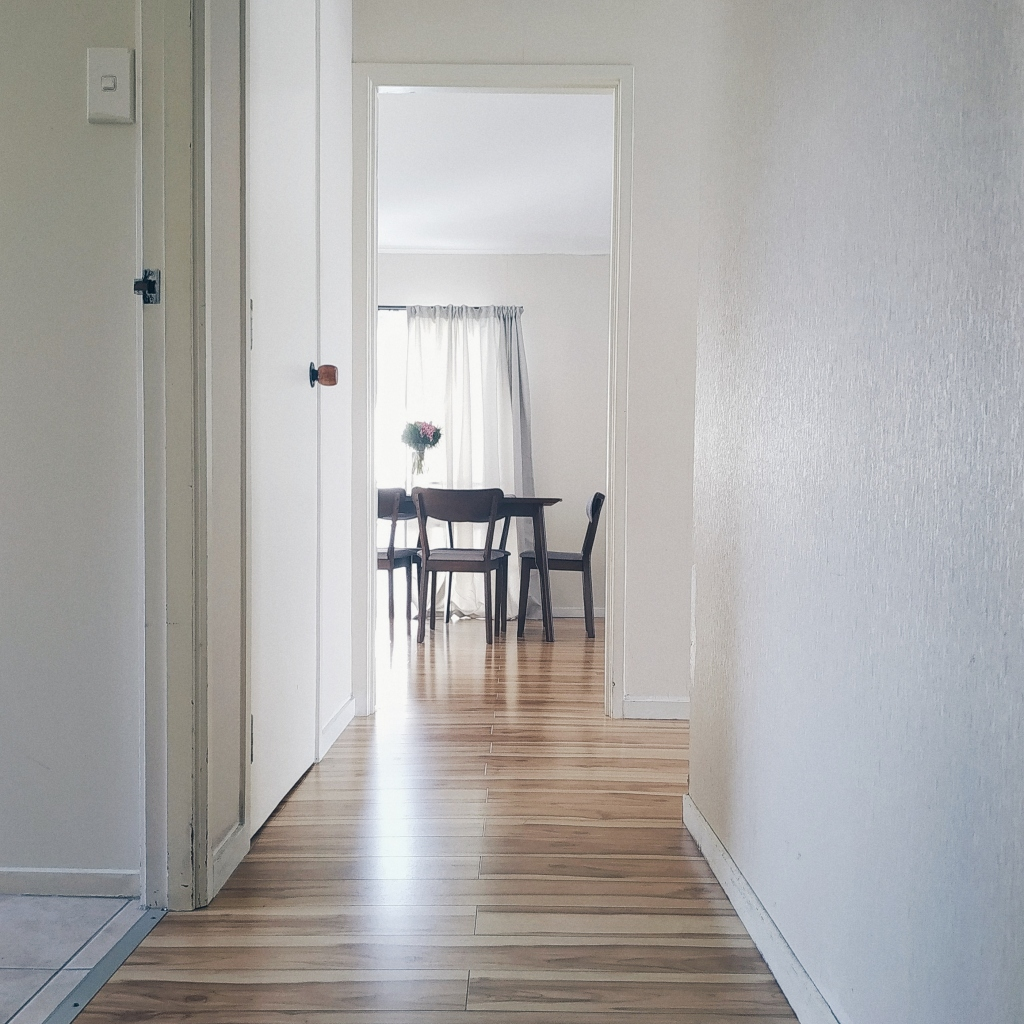 Hallway with white walls and a dining room at the end
