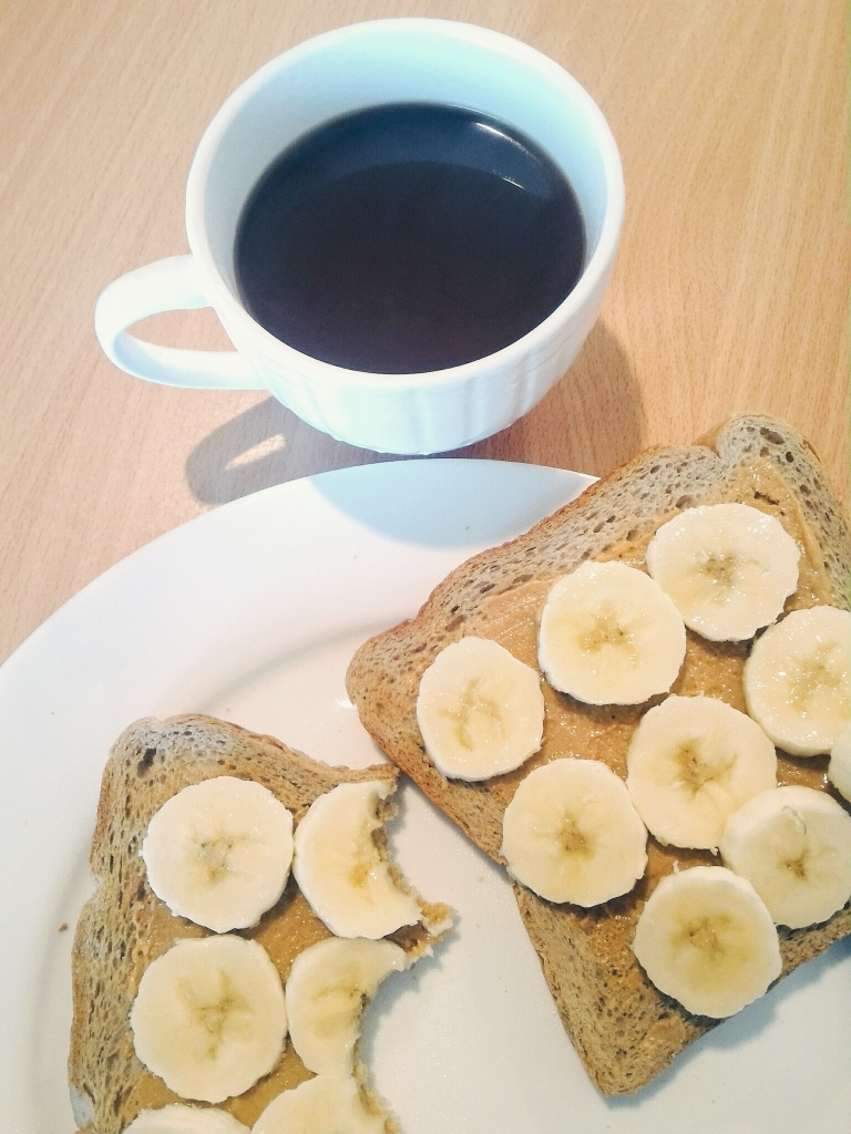 Black coffee, toast with peanutbutter and banana slices