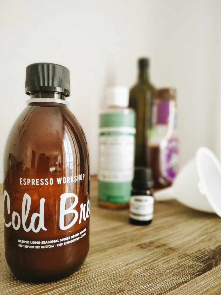 Homemade facial wash in a re-used cold brew glass bottle, with the ingredients at the back