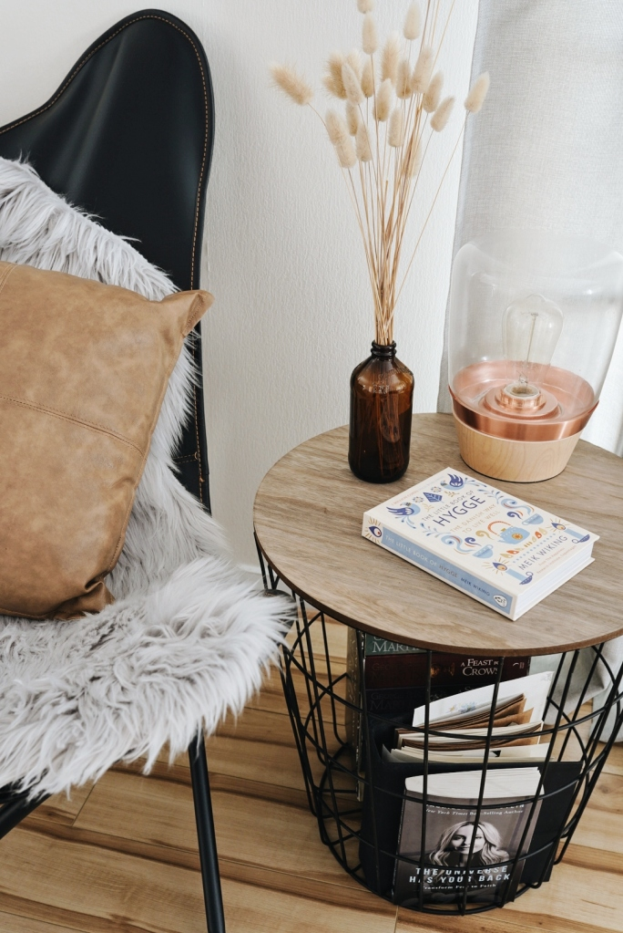 A chair with faux fur, a side table with a lamp, some dried plants and books.