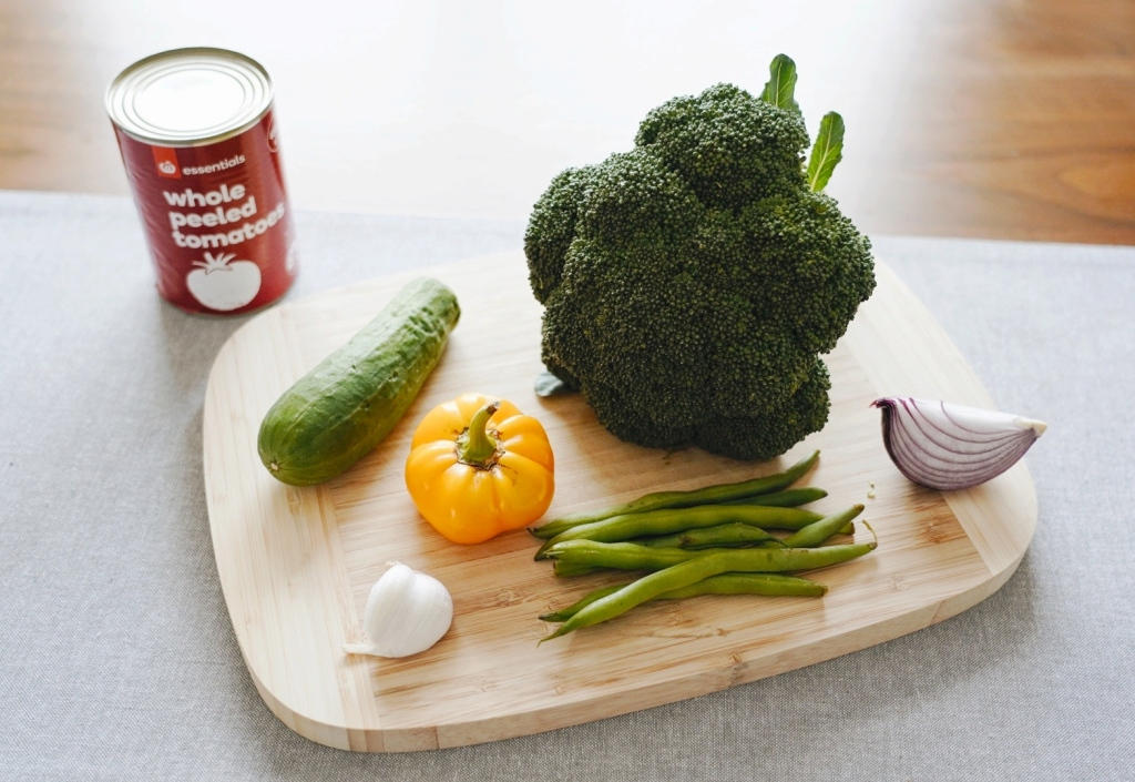 A can of whole tomatoes, and vegetables (cucumber, capsicum, broccoli, onion, beans, and garlic) on a chopping board
