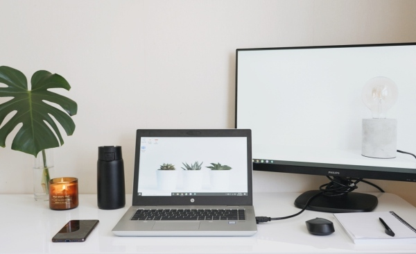A laptop, monitor, notebook, phone, plant, and candle